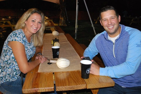 Couple enjoys food and beer at picnic table