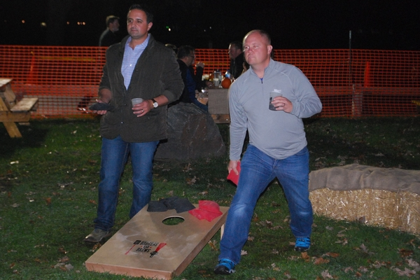Man and woman playing bags or corn hole at Brews & Bites